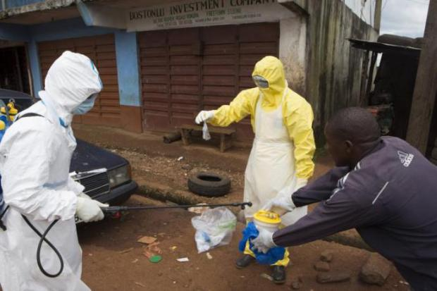 Health workers in protective suits handle a sample taken from the body of someone who is suspected of having died of the Ebola virus near Rokupa Hospital, Freetown, Sierra Leone, on Oct. 6, 2014. Reuters/Christopher Black